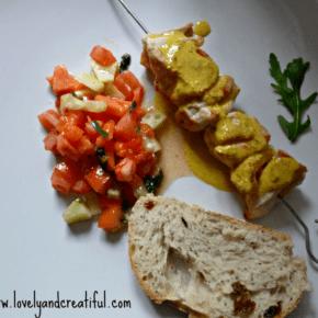 Brocheta de pollo con cobertura de yogur al curry y guarnición de papaya